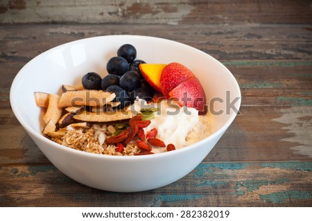 White bowl of fresh homemade banana and Greek yogurt muesli topped with fresh nectarine, goji berries, coconut and blueberries. This healthy and nutritious breakfast is served on a wooden tray. - stock photo