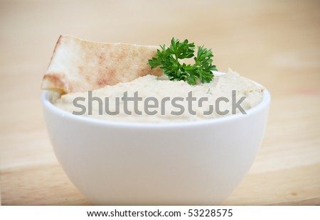 White Bowl of Hummus on a Butcher Block Table - stock photo