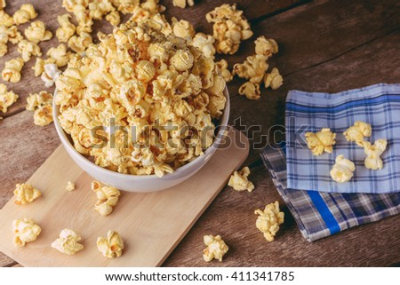 White bowl of popcorn on the wooden table, selective focus at popcorn in a bowl - stock photo