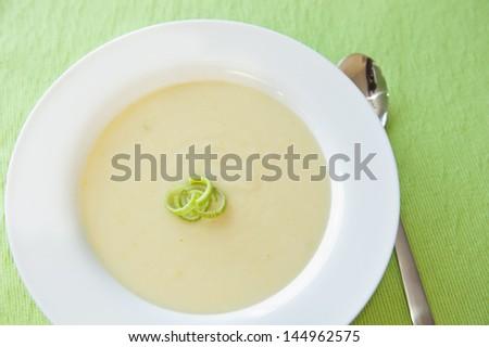 White bowl of potato leek soup on a green table cloth - stock photo