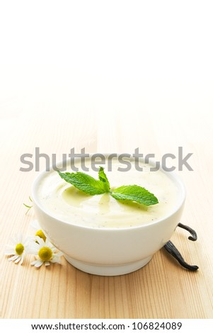 White bowl of vanilla yogurt on wood, with daisy blossoms, vanilla beans and mint leaves - stock photo
