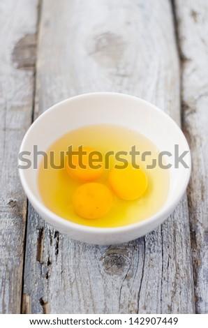 White bowl with cracked eggs - stock photo