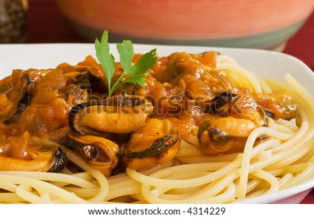 white bowl with noodles on tomato seafood sauce and mussel