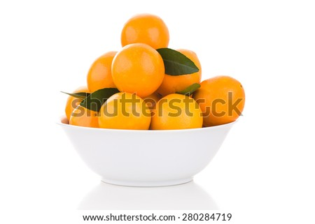 White bowl with oranges and leaves - stock photo
