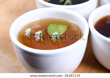 White Bowls of tea with mint leaves and twig