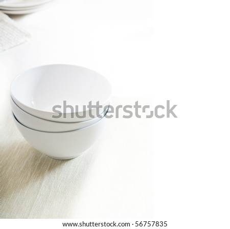white bowls stacked over white table cloth with dishes on background,huge wite copyspace - stock photo