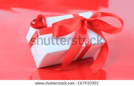 White box, bow, and ribbon for Valentine's Day or other events on red background