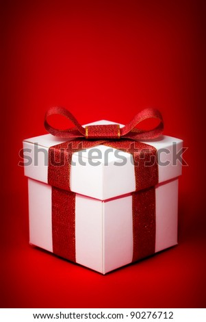 White box with a red ribbon on red background - stock photo