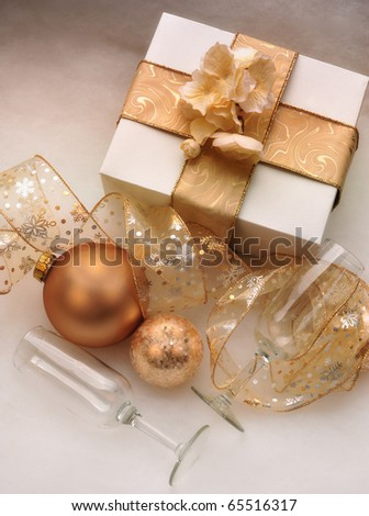 White box wrapped in a gold bow with champagne glasses and gold ornaments and ribbon - stock photo