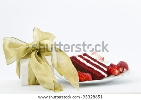 White box wrapped with gold ribbon is a special gift placed next to a slice of red velvet cake garnished with sliced strawberries - stock photo