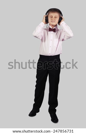 White boy listening to music with headphones on a gray background - stock photo
