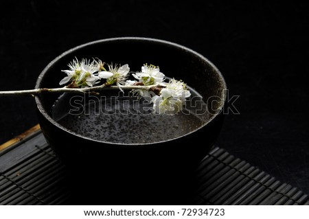 White branch cherry blossom in bowl on bamboo stick straw mat - stock photo