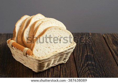 White bread in wicker wooden bowl on rustic table - stock photo