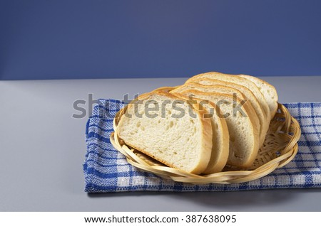 White bread in wicker wooden plate on kitchen table - stock photo
