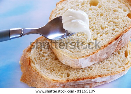 white bread slices with soft butter on spoon closeup