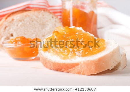white bread, spread with apricot jam - stock photo