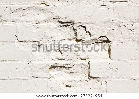 White brick wall textured background, closeup with cracks, breaks, holes, pattern - stock photo
