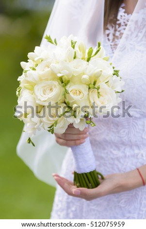 White bridal bouquet in the hands of the bride.