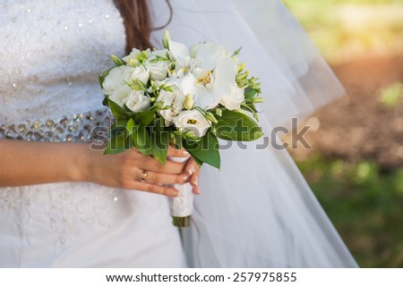 white bridal bouquet in the hands of the wedding. - stock photo