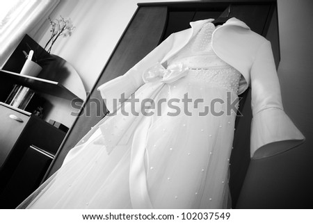 White bridal dress decorated with pearls and bow hanging in the room
