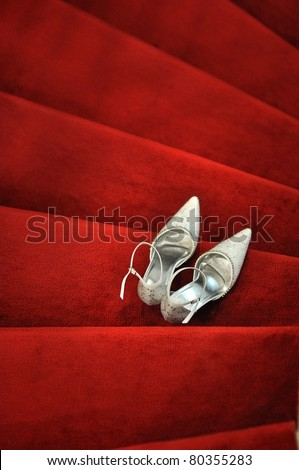 White bridal shoes on red carpet - stock photo