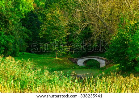 White Bridge over Small Green Pond in Park with Colorful Bushes and Trees