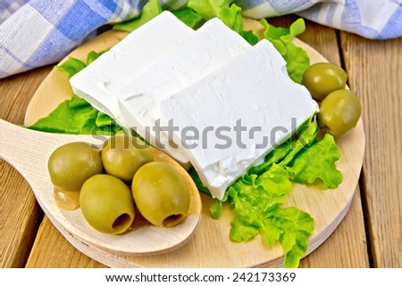 White brine cheese, lettuce, olives, spoon with olives, blue plaid napkin on a wooden boards background - stock photo