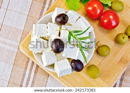 White brine cheese, olives, rosemary in a white bowl, tomatoes, lettuce, olives on a wooden boards background and tablecloth - stock photo