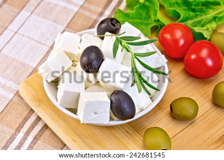 White brine cheese, olives, rosemary in a white bowl, tomatoes, lettuce, olives on a wooden boards background and fabrics - stock photo