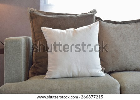 White, brown and grey velvet pillows setting up on sofa in living room interior - stock photo