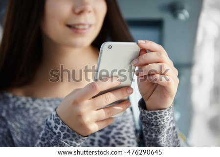 White brunette girl using modern smart phone. Close up focus on gadget, model unrecognizable
