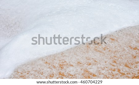 White bubbles created on the beach by ocean waves on seashore Foam bubbles abstract white background. Detergent white foam with some bubbles in it A wave thinning out of the sand of a beach - stock photo
