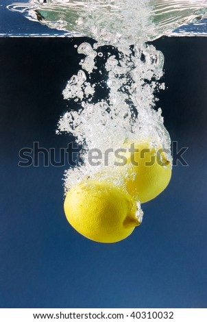 white bubbles from a couple of lemons sunk in water against a dark blue background - stock photo