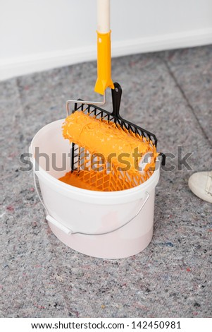 White bucket with orange paint and paint roller - stock photo