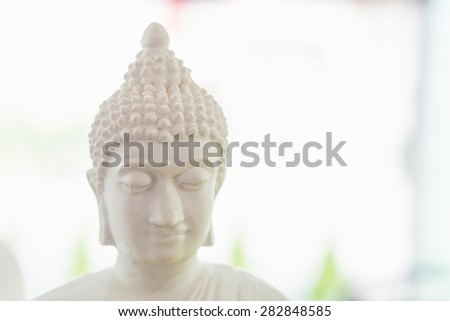 white buddha figure in blur background - stock photo