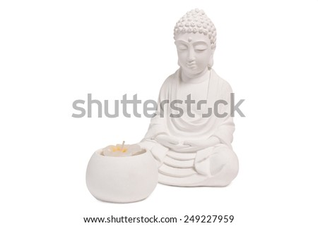 White Buddha figurine sitting in front of a candle - stock photo