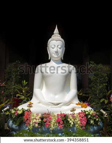 White buddha statue with flowers - stock photo