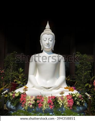 White buddha statue with flowers - stock photo