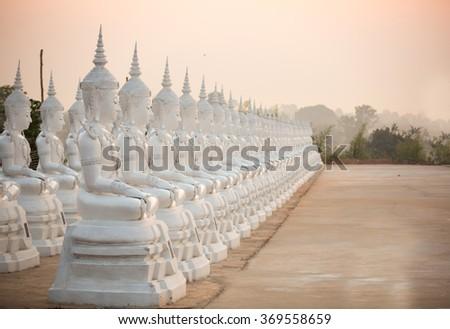 white Buddha statue with sunrise - stock photo