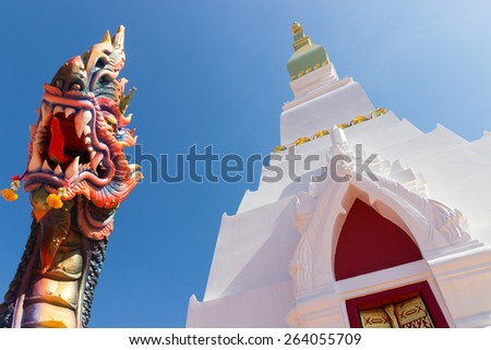 white buddhist pagoda and dragon statue with blue sky background - stock photo