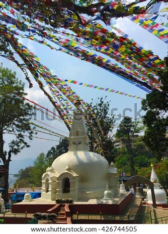 White buddhist stupa with colorful prayer's flags, white buddhist temple and flag ribbons, white and gold buddhist temple, buddhist temple with eyes, nepalese buddhist stupa, Kathmandu stupa with eyes - stock photo