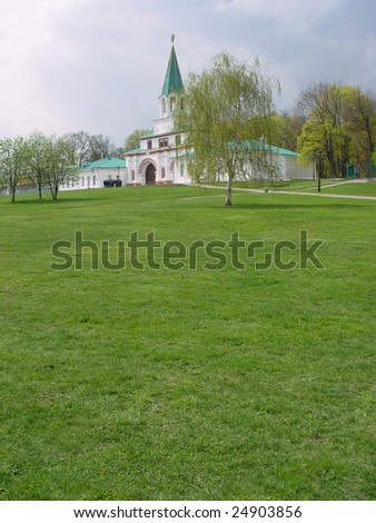 white building with a spire on the meadow