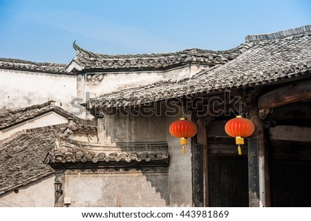 "White buildings with ornate roofs. Hongcun Village, China. An ancient picturesque village that has long enjoyed the name ""a village in the Chinese painting"" - stock photo"