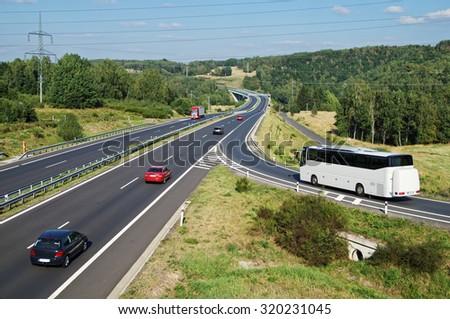 White Bus arriving to the asphalt highway on the slip road in a wooded landscape. Red passenger cars and truck driving on the highway. Electronic toll gate in the distance. View from above. - stock photo