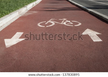 White bycicle symbol on a reddish cycle path - stock photo