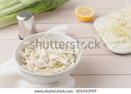 white cabbage cole slaw in white bowl on light wooden background - stock photo