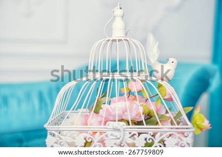White cage with flowers and bird as decoration on wedding.  - stock photo