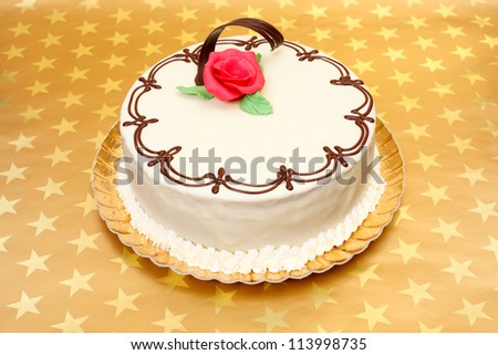 White cake with chocolate ornaments and red marzipan rose on golden stars background - stock photo