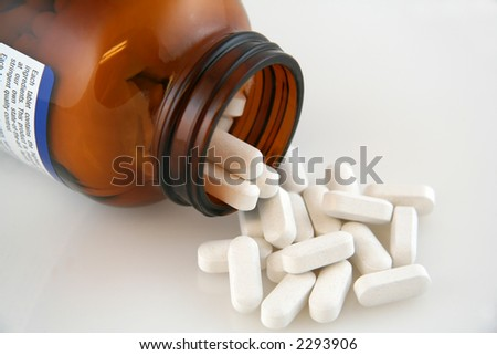 White Calcium Pills Pouring out of Bottle - stock photo