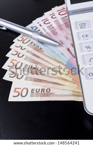 White calculator on top of euro banknotes on black background with silver pen - stock photo